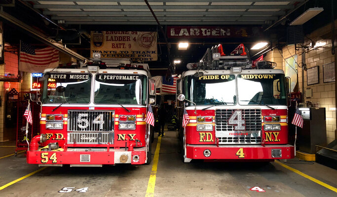 Two Firetrucks Sitting In the Fire Station Garage